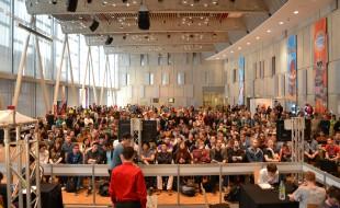 Eine gebannte Zuschauermenge während eines Feature Matches, zu sehen auf den Bildschirmen zum Publikum.